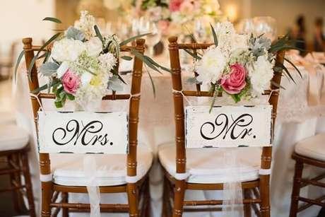 52. Plaquinhas de casamento para cadeira dos noivos e arranjo de flores. Fonte: Internovias