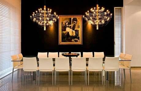 20. Decoração com dourado e preto para sala de jantar com mesa gigante. Fonte: Decoist