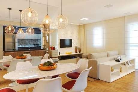 28. Neste ambiente integrada a iluminação de teto da sala de jantar com estrutura dourado chama a atenção. Projeto por Serra Vaz Arquitetura