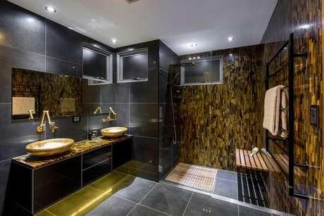 29. O dourado presente no revestimento da parede e no armário do banheiro encanta a decoração. Fonte: Pinterest