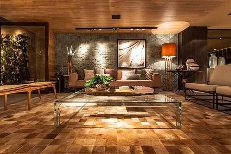 2. Sala de estar com mesa de centro de Vidro e tapete dourado. Projeto de Juliana Pippi