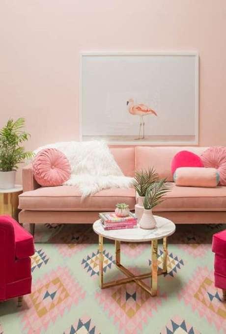 37. Sala de estar com sofá retrô na cor rosa e mesa de centro com pés em dourado. Fonte: Pinterest