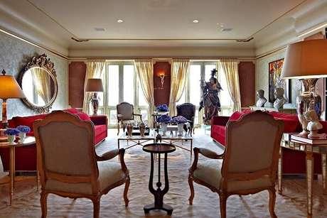38. Sala de estar com sofá vermelho e poltronas com acabamento na cor dourada. Projeto por SQ+ Arquitetos Associados