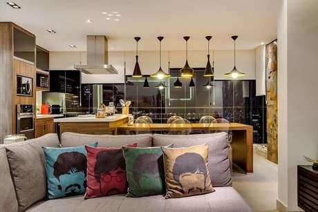 40. Sala de jantar com sala de estar integrada apresenta elementos na cor dourada. Projeto por Raduan Arquitetura