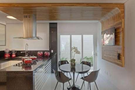 34. Parte da parede revestida de madeira também fica bem elegante. Projeto por Aquiles Nicolas Kilaris