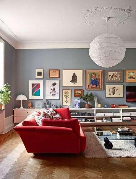 4. Decoração de sala com sofá vermelho e composição de quadros na parede – Por: Pecans Thome Deor