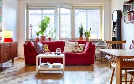 17. Sala ampla, com janelas e bastante iluminação para o sofá vermelho ficar ainda mais bonito – Por: DeaVita