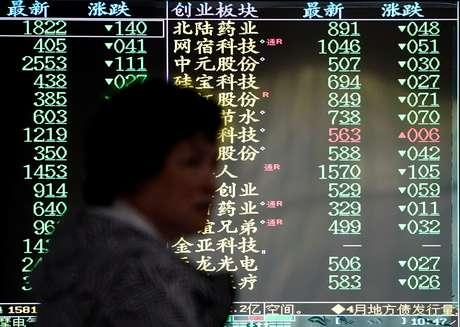 Investidora caminha em frente a painel eletrônico de ações em Xangai 06/05/2019 REUTERS/Aly Song
