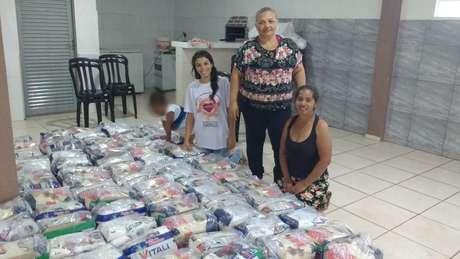 """""""No final da tarde elas me pedem, 'tia, tem um pãozinho aí para mim?' Se chega pão de doação, acaba tudo em um minuto"""", conta Maria Aparecida de Souza (de pé), líder comunitária no bairro."""