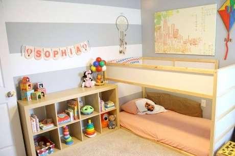 """56. Aqui, os móveis de madeira e os brinquedos quebram um pouco o ar """"frio"""" das paredes brancas e cinzas"""