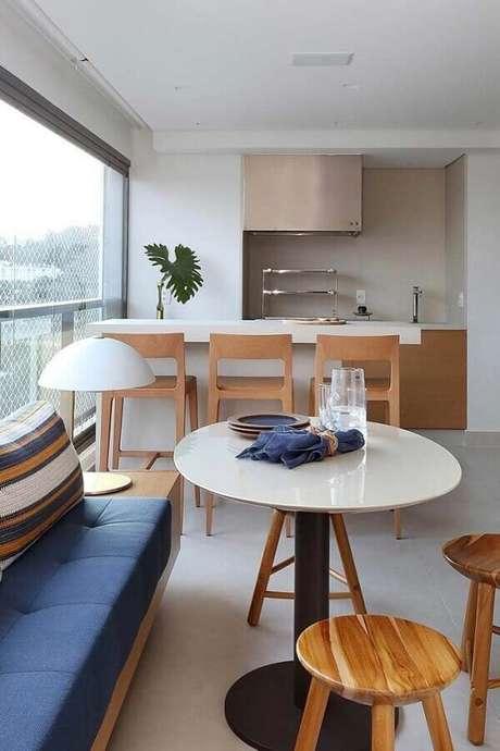 33. Decoração clean para espaço gourmet com banquetas de madeira e mesa redonda branca – Foto: Pinterest