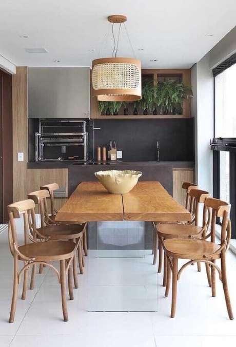 36. Decoração para espaço gourmet com mesa de madeira e churrasqueira – Foto: Ideias Decor