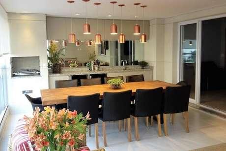 37. Decoração de espaço gourmet com parede espelhada e luminárias rose gold sobre mesa de madeira – Foto: Tatiana Baroni