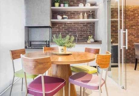 12. Decoração para espaço gourmet com mesa redonda de madeira e parede de tijolinho – Foto: Pinterest