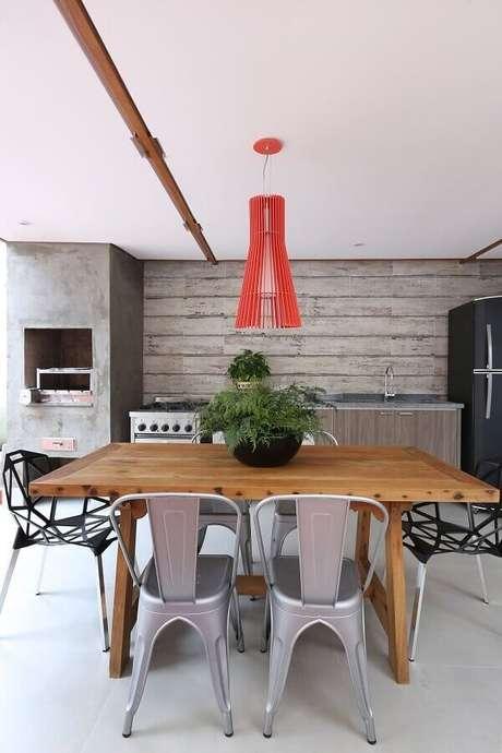 9. Decoração com estilo industrial para área gourmet com mesa de madeira e luminária vermelha – Foto: Antonio Armando de Araujo