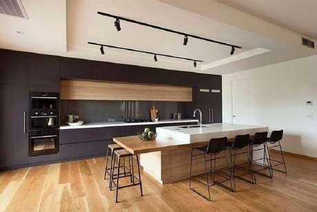 39. Decoração moderna para espaço gourmet amplo com bancada de madeira e spots de luz – Foto: R.Z. Owens Constructions