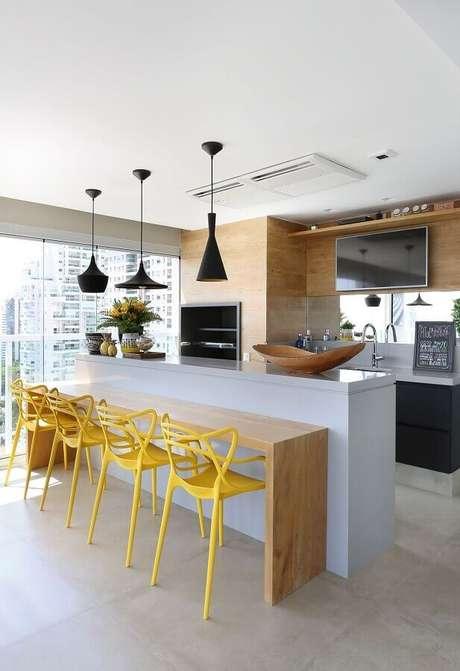 41. Decoração moderna para espaço gourmet com banquetas amarelas e pendentes pretos sobre bancada branca com detalhe em madeira – Foto: Karen Pisacane