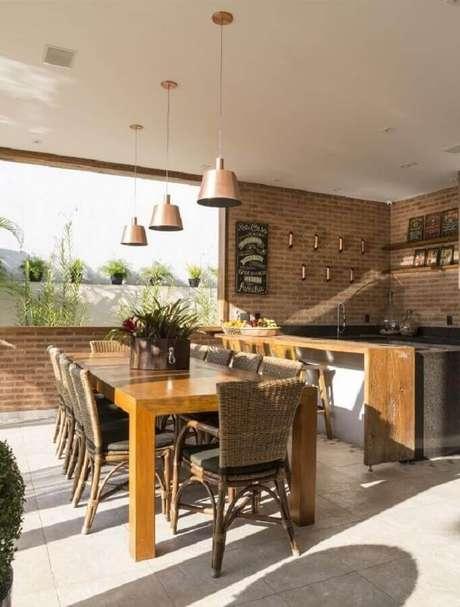 50. Decoração rústica para espaço gourmet com parede de tijolinho e luminárias sobre mesa de madeira – Foto: Studio Deux