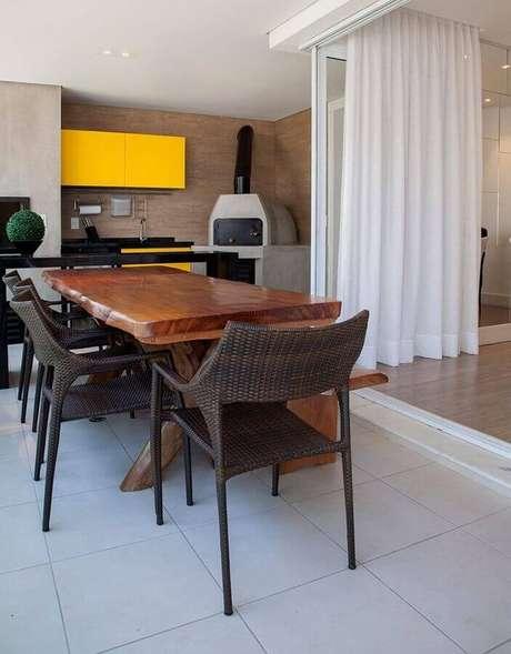 54. Espaço gourmet decorado com forno de pizza e mesa de madeira – Foto: GF Projetos