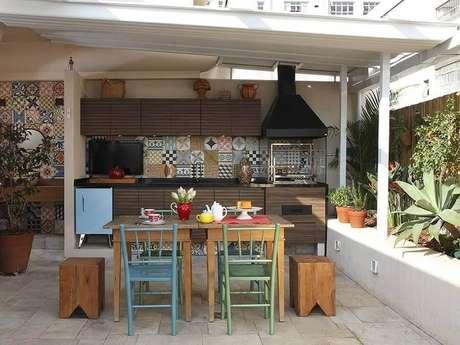 55. Espaço gourmet simples decorado com ladrilho hidráulico e mesa com cadeiras coloridas – Foto: Lore Arquitetura Lore