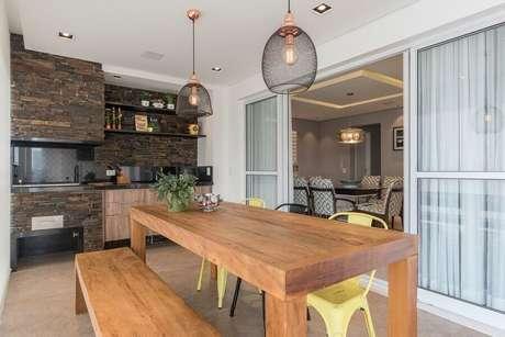 60. Espaço gourmet pequeno decorado com mesa de madeira e revestimento rústico – Foto: Idealizzare Arquitetos