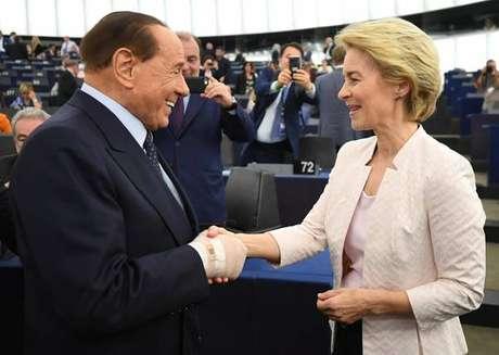 Silvio Berlusconi, com a mão enfaixada, cumprimenta a nova presidente da Comissão Europeia, Ursula von der Leyen