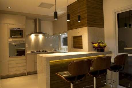 27. Bancada clara com iluminação embutida entre cozinha e sala. Projeto de Elevo Arquitetura