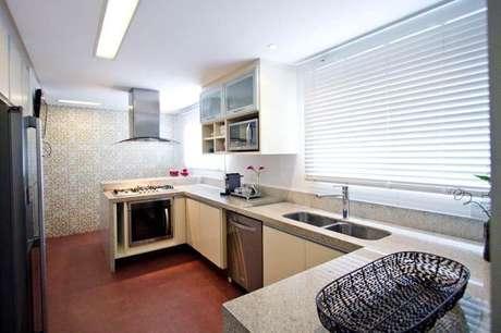28. Cozinha estilo corredor com bancada dessa pedra claro combinando com os armários. Projeto de Codecorar