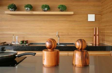 7. Cozinha gourmet revestida em madeira e bancada de granito preto. Projeto de Sandra Picciotto