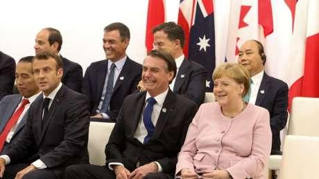 Bolsonaro (centro) com Emmanuel Macron (esq.) e Angela Merkel (dir) no Japão: presidente perderia a aposta a respeito da Amazônia