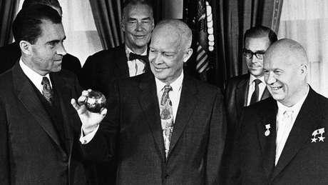 Um presente jocoso: olhado pelo premiê soviético Khrushchev (à direita) e pelo vice-presidente Richard Nixon (esquerda), Dwight Eisenhower segura uma cópia da esfera enviada à Lua a bordo da Luna 2, em 1959