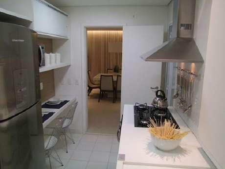 72. Cozinha compacta com bancadas brancas e aço inox. Projeto Cristina Marcovecchio