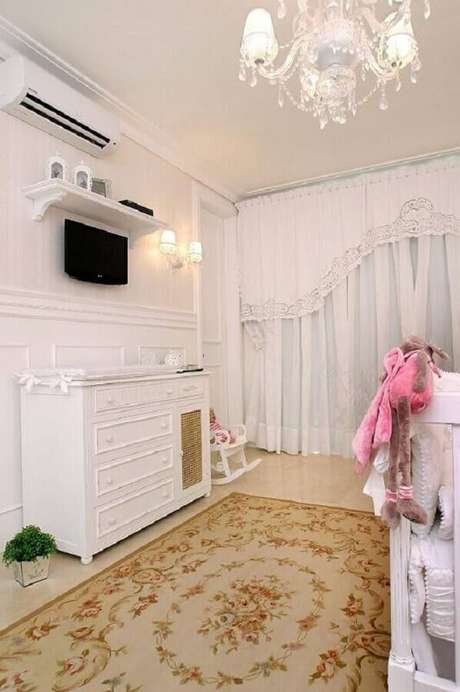 27. Decoração clássica com cômoda branca para quarto de bebê todo branco com lustre e tapete floral – Foto: Nicolle do Vale