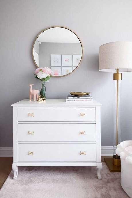 37. Decoração clean com cômoda branca com puxador em formato de laço e espelho redondo – Foto: Decorpad
