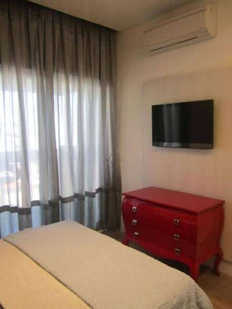 49. Decoração simples com cômoda vermelha e TV – Foto: Sueli Porwjan