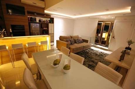 10. A mesa retangular branca da sala de jantar serve para dividir ambientes. Projeto por Cristina Reinert