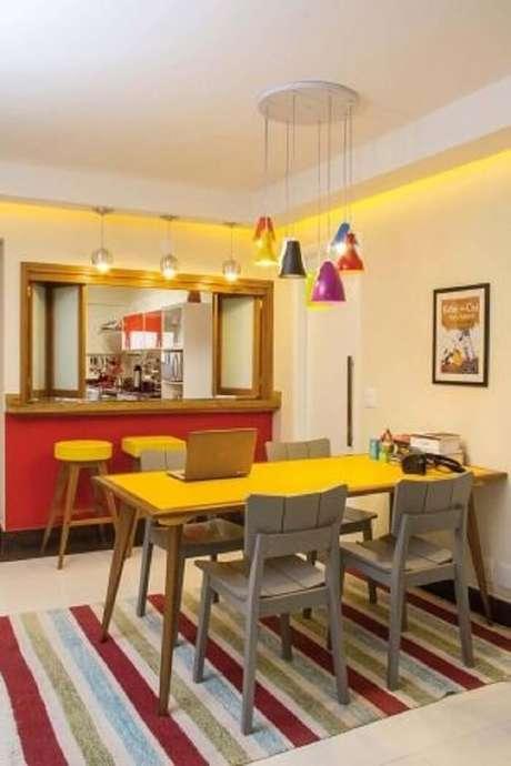 11. A mesa retangular com tampo amarelo combina com o tecido das banquetas. Projeto Move Móvel