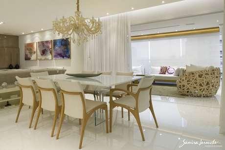 7. A mesa retangular da sala de jantar se integra ao ambiente da varanda. Projeto por Samira Jarouche