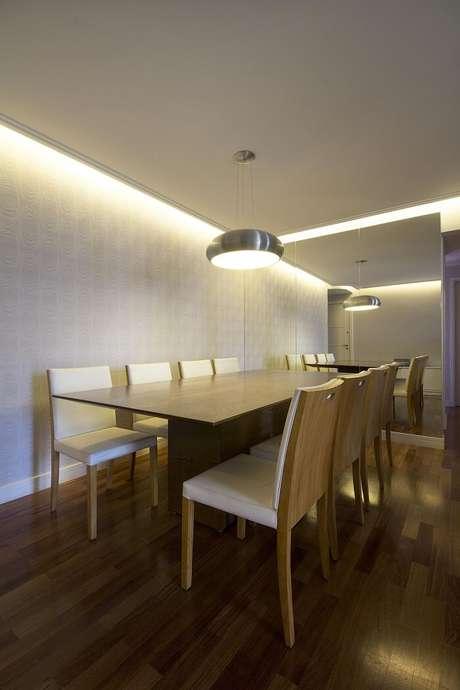 14. A mesa retangular de madeira complementa a decoração da sala de jantar. Projeto por Juliana Conforto