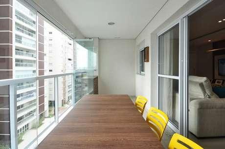 16. A varanda deste apartamento conta com a presença de uma mesa retangular de madeira. Projeto por Condecorar Arquitetura e Interiores