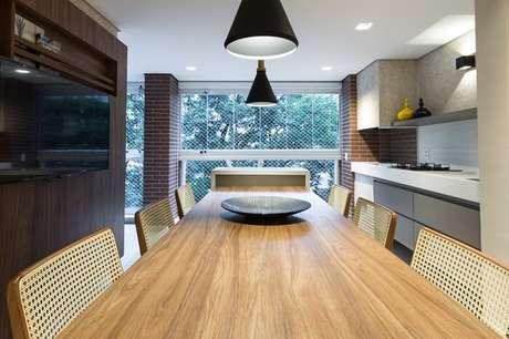 21. Cozinha integrada com a varanda com mesa retangular de madeira. Projeto por Marília Veiga