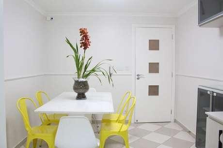 28. Mesa retangular branca e cadeiras amarelas para o ambiente de cozinha. Projeto por Amanda Pagliarini Macedo