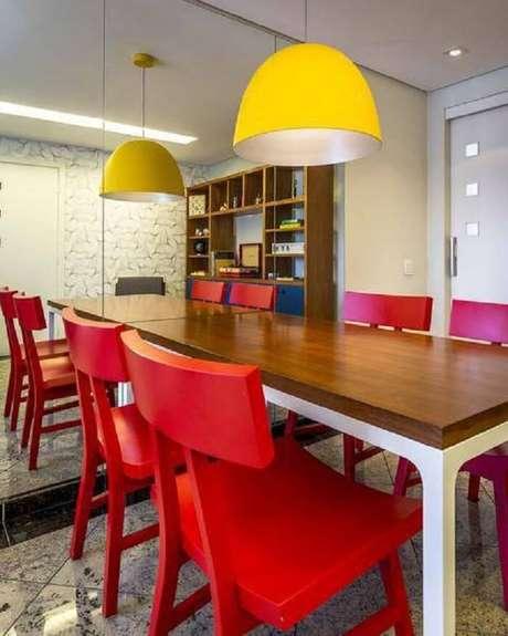 67. Mesa retangular com tampo de madeira e cadeiras na cor vermelha. Projeto de Enzo Sobocinski