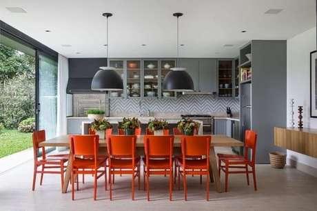 37. Mesa retangular de madeira com cadeiras na cor vermelho. Fonte: Marina Linhares