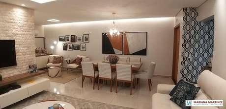 56. O design da mesa retangular da sala de jantar se harmoniza com a decoração do ambiente. Projeto por Mariana Martinez
