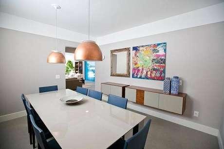 74. Sala de jantar com mesa retangular branca e cadeiras na cor azul. Fonte: Pinterest