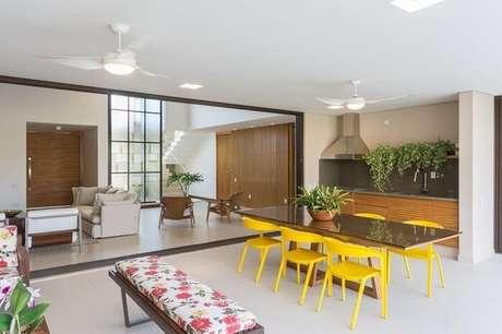 64. Varanda integrada conta com a presença de uma mesa retangular de madeira com tampo de vidro e cadeiras amarelas. Projeto por Jannini Sagarra Arquitetura