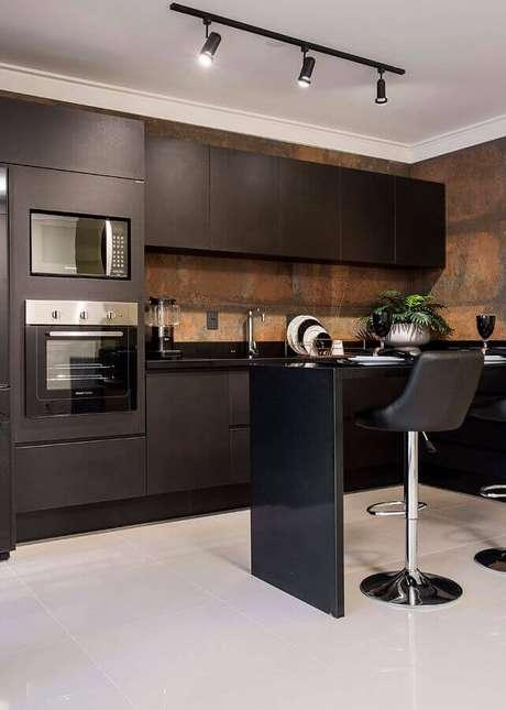 13. Cozinha planejada toda preta decorada com aço corten e forno elétrico embutir – Foto: Total Construção