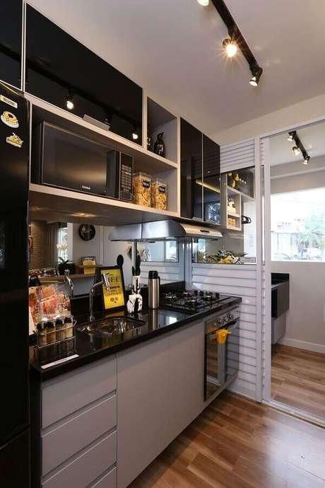 14. Decoração de cozinha planejada preta e cinza com spots de luz e forno elétrico embutir – Foto: Imovelweb