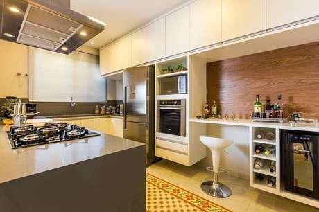 20. Decoração cozinha planejada com armário branco, revestimento em madeira e forno elétrico de embutir inox – Foto: BY Arq&Design